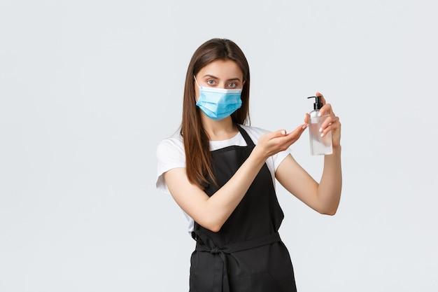 Covid-19社会的距離、カフェの従業員、コーヒーショップ、コロナウイルスのコンセプト。真面目なレジ係、黒いエプロンのバリスタ、医療用マスク、手の消毒剤を使って手を洗う方法を示しています