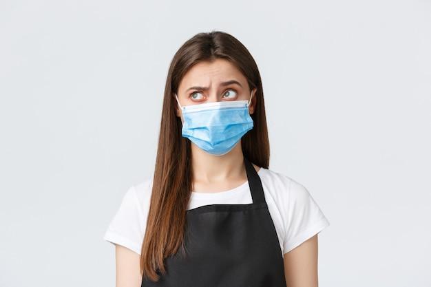 Социальное дистанцирование covid-19, сотрудники кафе, кафе и концепция коронавируса. скептически и сомнительно симпатичная кассирша в медицинской маске, продавщица неуверенно смотрит в левый верхний угол