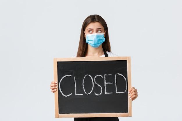 Социальное дистанцирование covid-19, сотрудники кафе, кафе и концепция коронавируса. расстроенная милая женщина-бариста в медицинской маске грустно смотрит в сторону, показывая, что мы закрыты, знак, не можем открыть во время пандемии