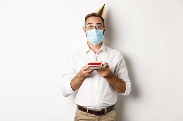 Covid-19, allontanamento sociale e celebrazione. ragazzo sorpreso di compleanno che tiene la torta di compleanno, che indossa la maschera per il viso dal coronavirus, sfondo bianco.