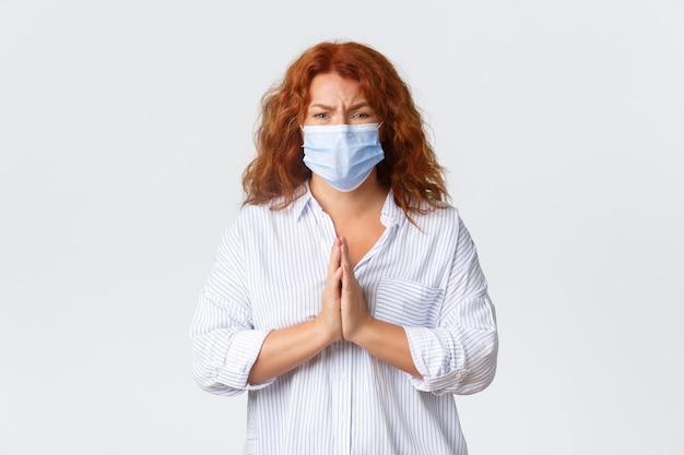 Covid-19の社会的距離、コロナウイルス予防策および人々の概念。医療用マスクを身に着けた希望に満ちた心配中年の女性、助けを懇願する赤い髪の女性、好意を訴える。
