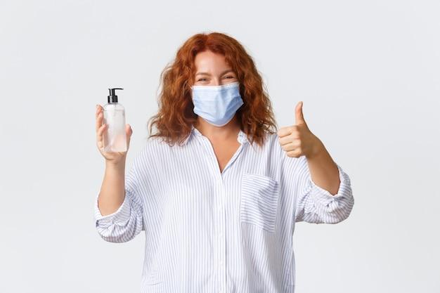Covid-19の社会的距離、コロナウイルス予防策および人々の概念。笑顔のかわいい中年赤毛の女性は、親指を立てて医療用マスクを着用し、手指消毒剤をお勧めします。