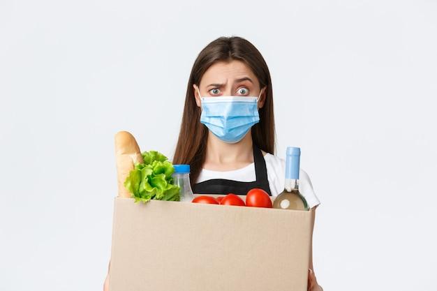 Covid-19 социальное дистанцирование, доставка и покупка продуктов во время концепции коронавируса. смущенная и шокированная продавщица, кассир в медицинской маске, поднимая бровь, держа коробку с продуктами.