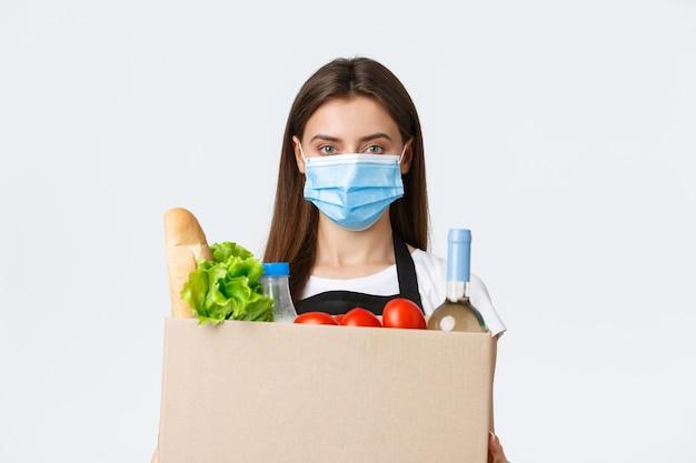Covid-19 социальное дистанцирование, доставка и покупка продуктов во время концепции коронавируса. молодая приятная продавщица, кассир в медицинской маске, передающая продукты покупателю