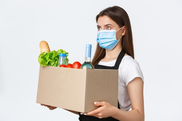 Социальное дистанцирование covid-19, сотрудники и покупка продуктов во время концепции коронавируса. профиль продавщицы в черном фартуке и медицинской маске, держащей коробку с заказом продуктов для клиентов