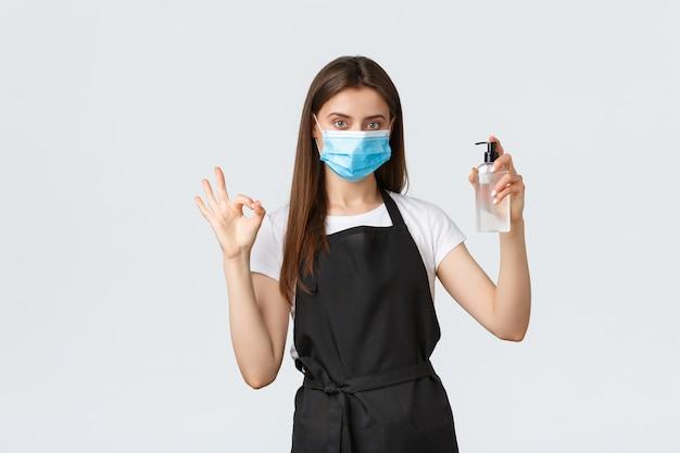 Covid-19 социальное дистанцирование, сотрудники, кафе, концепция коронавируса. бариста или официантка в медицинской маске показывает дезинфицирующее средство для рук и показывает знак ок, чтобы гарантировать соблюдение всех мер по предотвращению вирусов.