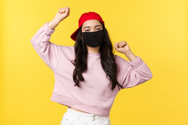Covid-19, social-distancing lifestyle, prevent virus spread concept. carefree excited asian woman in red cap and face mask, dancing with hands raised up, having good summertime
