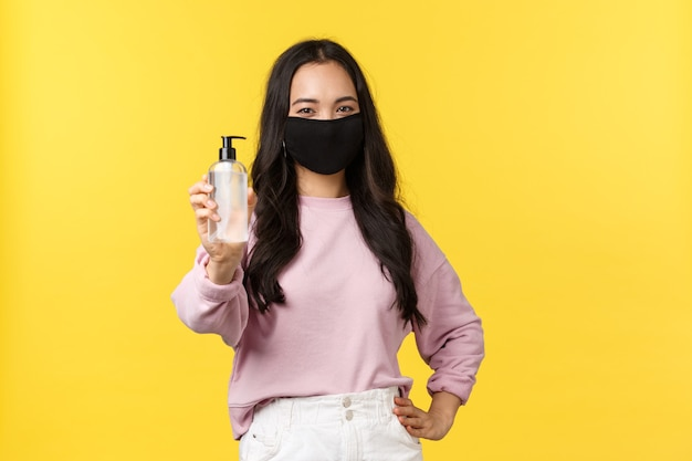 Covid-19, social-distancing lifestyle, prevent virus spread concept. cheerful asian girl in face mask always using hand sanitizer during coronavirus pandemic, recommend hygiene product.