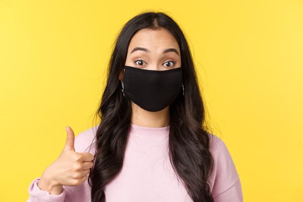 Covid-19, stile di vita a distanza sociale, previene il concetto di diffusione del virus. primo piano di una ragazza asiatica entusiasta in maschera facciale, sembra sorpresa e divertita, mostrando il pollice in su in segno di approvazione, sfondo giallo
