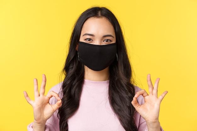 Covid-19、社会距離拡大のライフスタイルは、ウイルス拡散の概念を防ぎます。フェイスマスクで幸せな笑顔のアジアの女性のクローズアップ、すべてを制御下に置き、のように大丈夫なサインインを示し、お勧めします。
