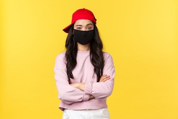 Covid-19、社会的距離のあるライフスタイルは、ウイルス拡散の概念を防ぎます。フェイスマスクと赤い帽子の懐疑的で疑わしいアジアの女性、胸をクロスし、信じられないほど眉を上げる