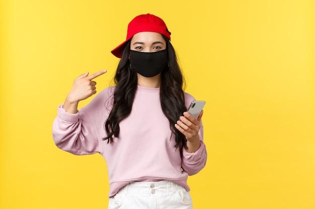 Covid-19, образ жизни с социальным дистанцированием, концепция предотвращения распространения вируса. улыбающаяся милая азиатская девушка указывает на маску для лица, просит защитить здоровье во время коронавируса, держит мобильный телефон, желтый фон