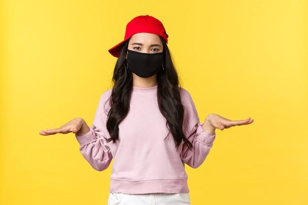 Covid-19、社会距離拡大のライフスタイルは、ウイルス拡散の概念を防ぎます。フェイスマスクと赤い帽子をかぶった、気ままな若いアジアの女の子は、低いままで、何か小さな黄色の背景を示しています。