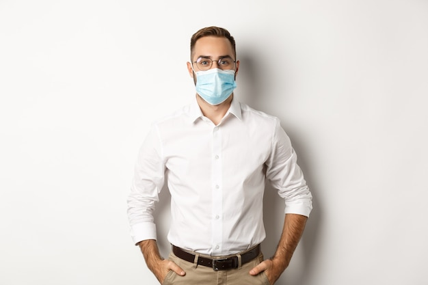 Covid-19, social distancing and quarantine concept. male employee wearing face mask for work, standing against white background.