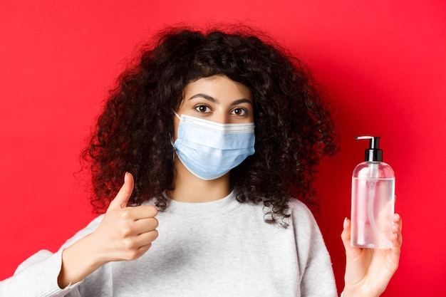 Covid-19, social distancing and quarantine concept. portrait of woman in face mask from coronavirus, showing hand sanitizer bottle and thumb up, recommending antiseptic.