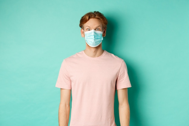 Covid-19, social distancing and quarantine concept. young man raising eyebrows and looking surprised, wearing face mask during pandemic, standing over mint background.