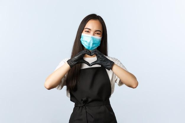 Covid-19、社会的距離、小さな喫茶店ビジネス、ウイルスの概念の防止。キュートで優しいバリスタ、アジアの女性カフェスタッフが訪問者の世話をし、ハートサインを見せ、医療用マスクと手袋を着用します。