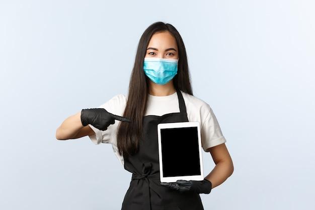 Covid-19, социальное дистанцирование, небольшая кофейня и концепция предотвращения вирусов. симпатичный молодой азиатский бариста, женский работник кафе в медицинской маске, указывая на цифровой планшет