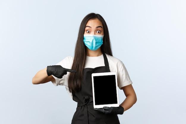 Covid-19、社会的距離、小さなコーヒーショップのビジネスとウイルスの概念を防ぎます。興奮しているアジアのバリスタ、医療マスクとデジタルタブレットを指している手袋の女性カフェワーカー、驚いて見える