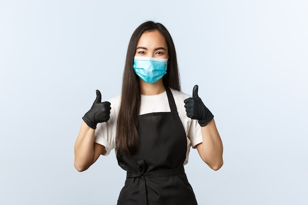코비드-19, 사회적 거리, 소규모 커피숍 사업, 바이러스 개념 예방. 친절한 미소 짓는 아시아 카페 주인, 바리스타는 코로나바이러스로부터 모든 것을 안전하게 보호하고 의료 마스크와 장갑을 착용합니다