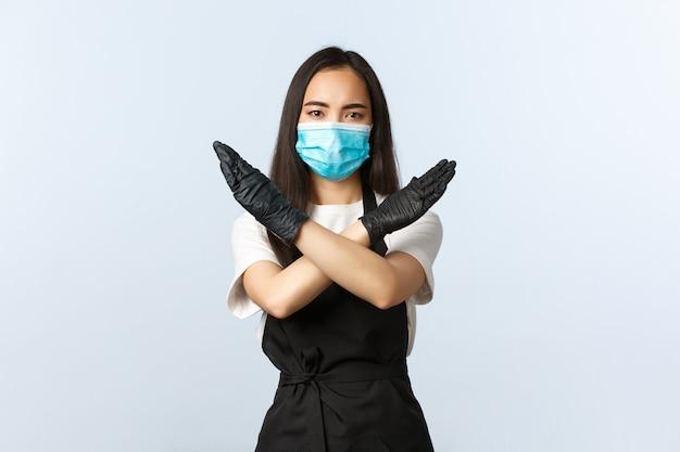 Covid-19、社会的距離、小さな喫茶店ビジネス、ウイルスの概念の防止。真面目な若いバリスタ、アジアのカフェスタッフは、顧客が医療用マスクなしで中に入ることを禁止し、クロスストップサインを表示します