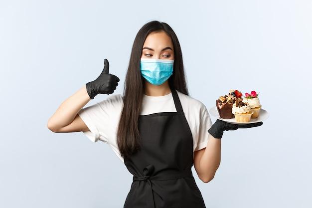 Covid-19, социальное дистанцирование, небольшая кофейня и концепция предотвращения вирусов. улыбающаяся азиатская владелица пекарни, работница кафе в медицинской маске и перчатках рекомендуют вкусные кексы.
