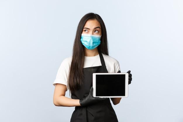 Covid-19, социальное дистанцирование, небольшая кофейня и концепция предотвращения вирусов. задумчивая владелица азиатского женского кафе, бариста смотрит вверх, думает, показывает экран цифрового планшета, онлайн-доставка