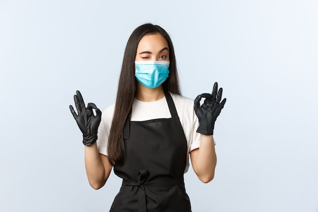 Covid-19, social distancing, small coffee shop business and preventing virus concept. cheeky asian waitress, barista in medical mask and gloves show okay sign, wink assuring, guarantee cafe safety