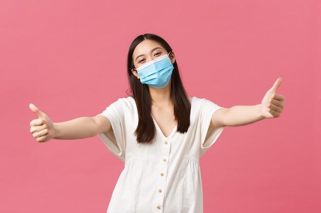 Covid-19、社会的距離、ウイルス、ライフスタイルの概念。医療マスクと夏のドレスでフレンドリーな幸せなアジアの女性は、抱擁を与えるために手を伸ばし、誰かを歓迎し、ピンクの背景に立っています