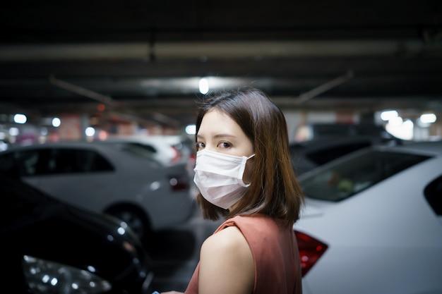 Распространение covid-19. женщина в медицинской защитной маске на стоянке. страх коронавируса.