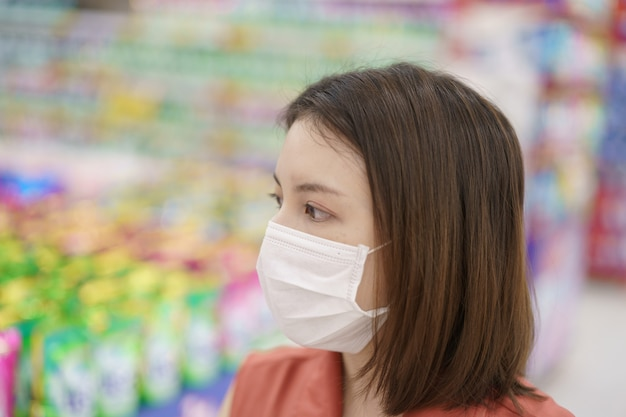 Covid-19 spreading outbreak. woman in medical protective mask panic buying food. fear of coronavirus.