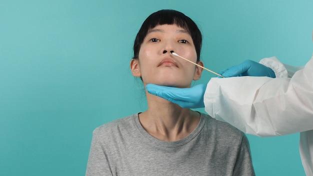 Covid 19 면봉 테스트. Pcr 테스트를 가진 여자입니다. 전염병 중 코로나 바이러스 검사. 메딕은 바이러스 검사를 위해 샘플을 채취합니다. 스튜디오 촬영 및 파란색 녹색 배경입니다. Ppe 정장 면봉 테스트 의사. 프리미엄 사진