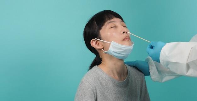 Covid 19 면봉 테스트. pcr 테스트를 가진 여자입니다. 전염병 중 코로나 바이러스 검사. 메딕은 바이러스 검사를 위해 샘플을 채취합니다. 스튜디오 촬영 및 파란색 녹색 배경입니다. ppe 정장 면봉 테스트 의사.