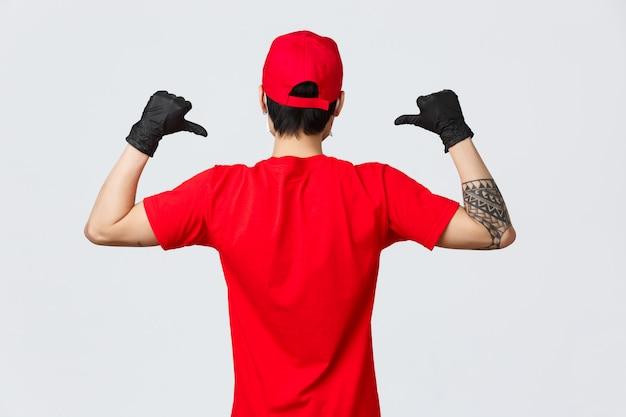 パンデミックcovid-19中に保護手袋を着用して、赤い帽子とtシャツの配達人の背面図。