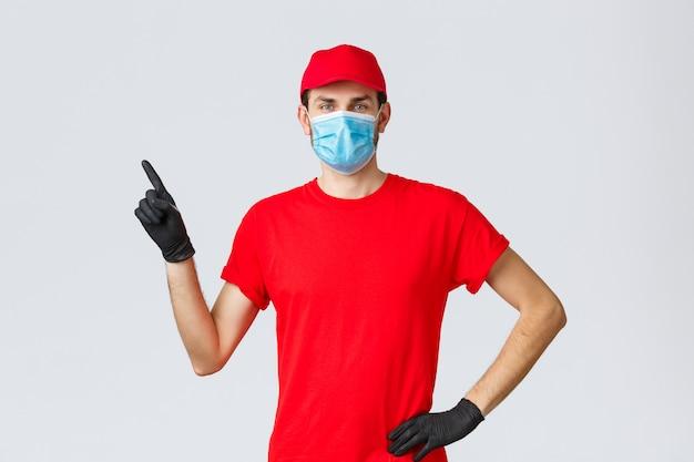 Covid-19、自己検疫、オンラインショッピング、配送のコンセプト。赤い帽子とtシャツ、クライアントと従業員を保護するための手袋が付いた医療用マスク、プロモーションで左指を指している広告を表示する配達人