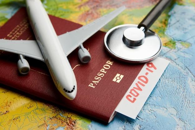 パスポートと医療聴診器で世界地図の背景にcovid19渡航文書。コロナウイルスパンデミック旅行のコンセプト。 covid-19医療検査