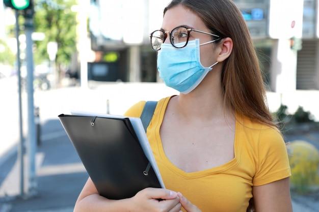 Covid-19大通りを歩く外科用マスクの大学生女性。