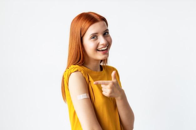 Covid-19 вакцинированная кавказская счастливая улыбающаяся молодая женщина, показывающая руку с гипсом, серый фон