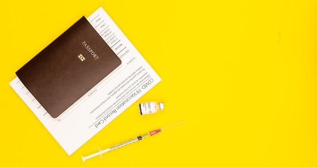 Covid-19 예방 접종 기록 카드 증명서와 코로나바이러스 백신 병 및 주사기가 있는 여권은 복사 공간이 있는 노란색 배경에 함께 제공됩니다. 상위 뷰 및 평면 누워 샷입니다.
