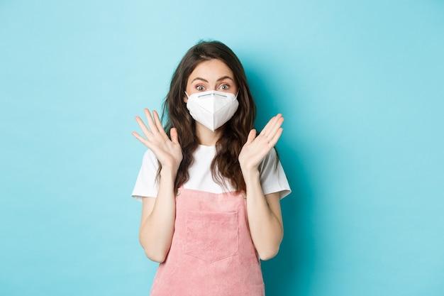 코비드-19, 예방 접종 및 검역 개념. 의료 호흡기를 착용한 흥분되고 놀란 젊은 여성, 코로나바이러스의 얼굴 마스크, 박수를 치고 카메라, 파란색 배경에 놀란 표정