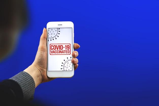 Вакцинация от covid-19 в мире, женщина держит смартфон с концепцией цифрового приложения паспорта здоровья, копией космической фотографии