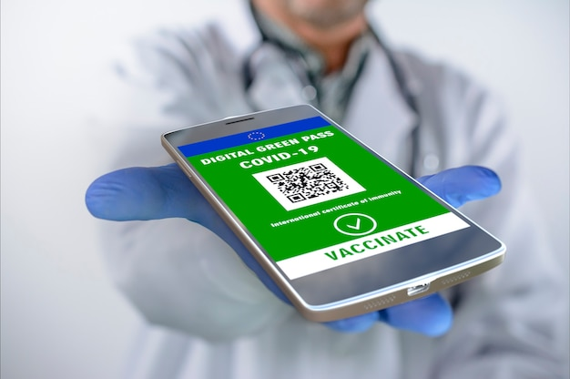Covid-19 vaccination passport on mobile phone for travel, doctor holds smartphone with health certificate application, coronavirus digital pass. digital green pass