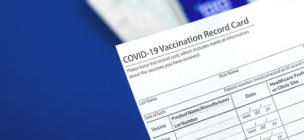 Covid-19 vaccination record card close up on table in hospital, banner
