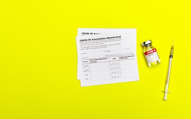Карточка учета вакцинации против covid-19, включая информацию о пациенте, дозе, партии продукта, дате инъекции, клинике, медицинском работнике рядом со стаканом для вакцины и медицинским шприцем.