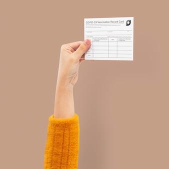 Certificato di vaccino contro il covid-19 tenuto dalla mano di un uomo d'affari