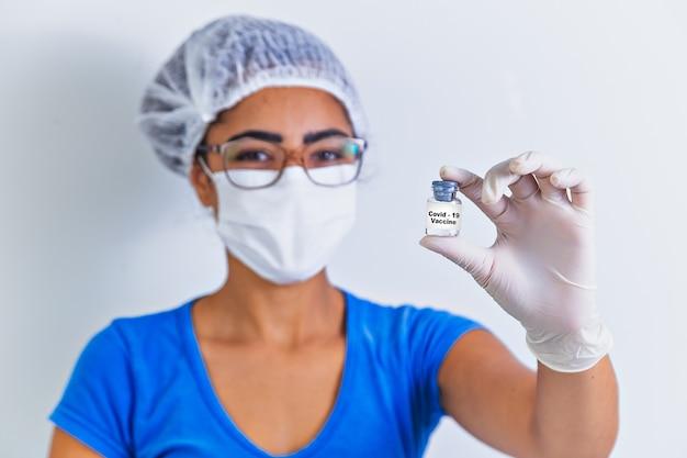 연구원의 손에 covid-19 백신, 여성 의사는 코로나 바이러스 치료를 위해 주사기와 백신 병을 들고 있습니다. 대유행 중 코로나 바이러스 치료, 주사, 주사 및 임상 시험의 개념.