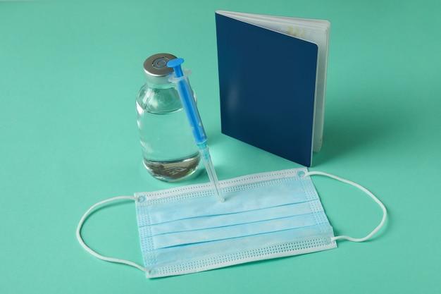 민트 배경에 covid-19 백신, 주사기, 마스크 및 여권
