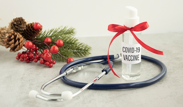 Covid-19 vaccine text on jar with red ribbon, new year concept and covid vaccination