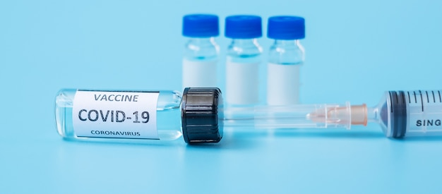Covid-19病院の実験室でのコロナウイルス感染に対するワクチンバイアルと注射針注射器。医療、健康、予防接種、予防接種の概念