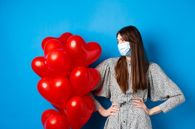 Covid-19 e san valentino. giovane ragazza infastidita in maschera medica e vestito, guardando i palloncini del cuore, in attesa della data, in piedi sullo sfondo blu